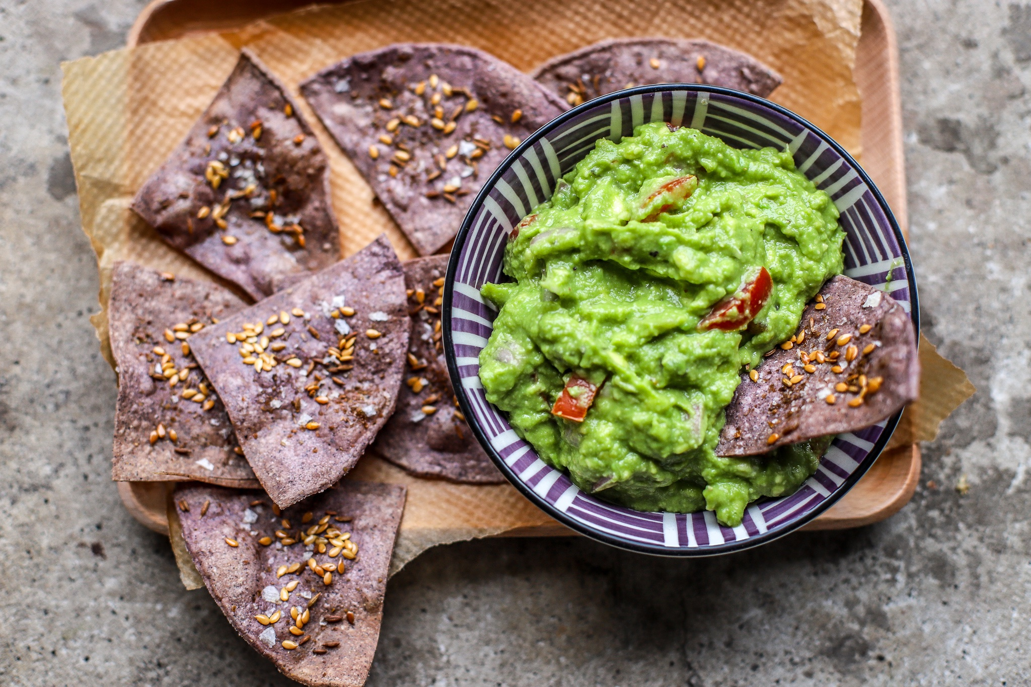 green tea guacamole with homemade purple tortilla chips on wooden tray