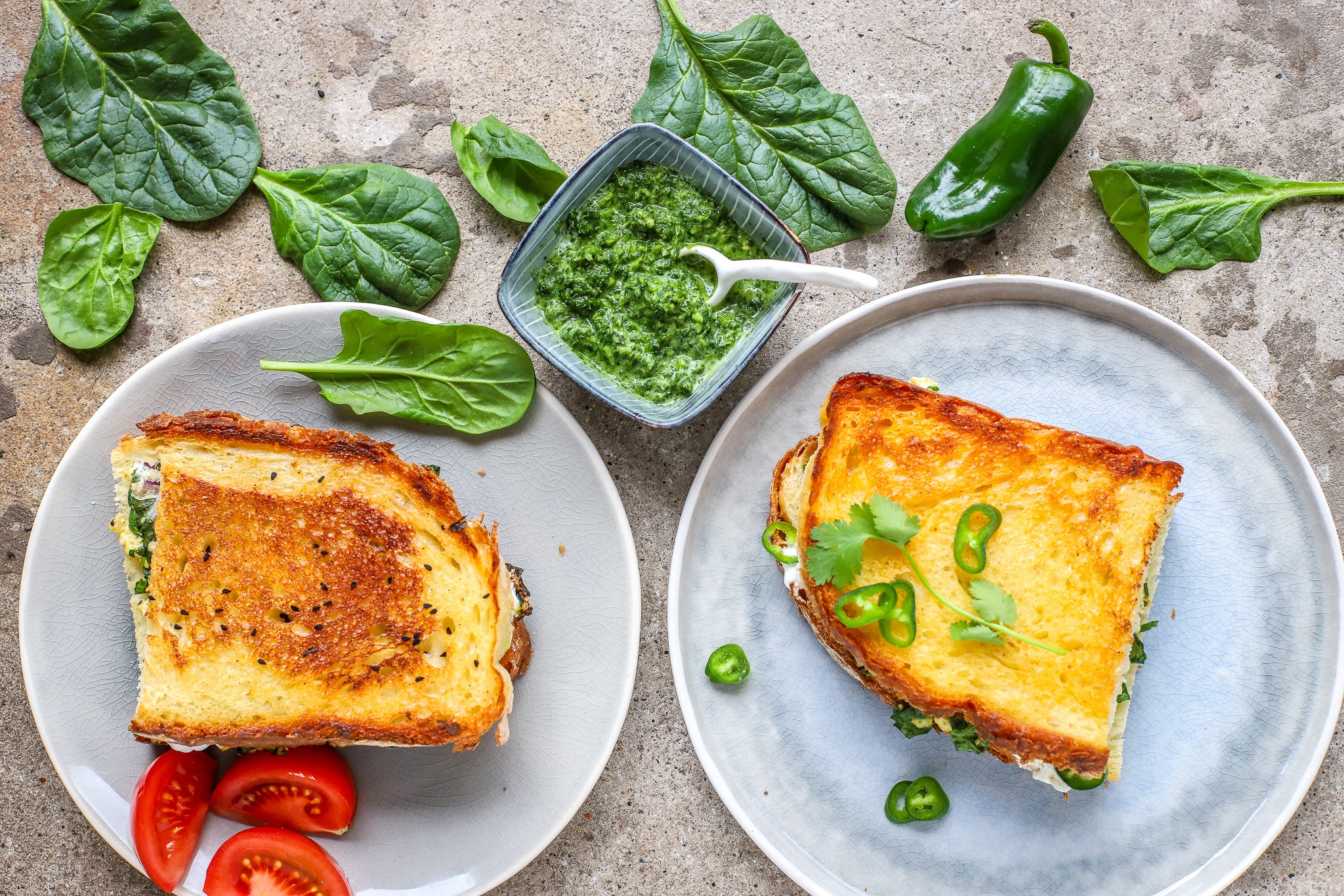sliced grilled cheese sandwich with paneer and spinach on plates with green chillies and spinach leaves surrounding them.
