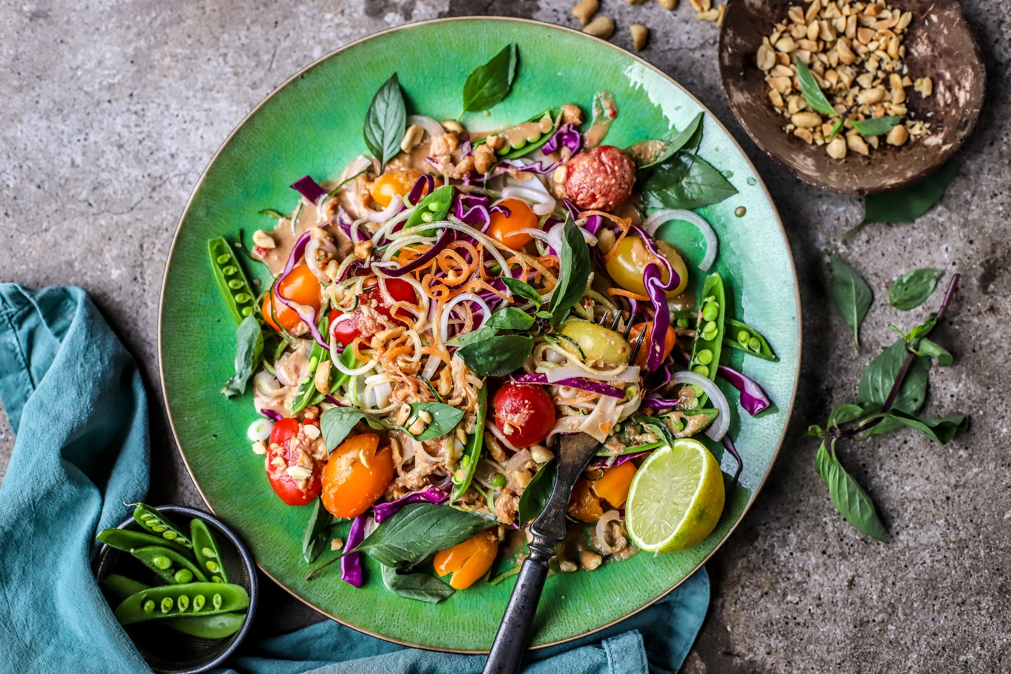 Flatlay wide view of Thai noodle salad with colourful veg on green plate with green napkin