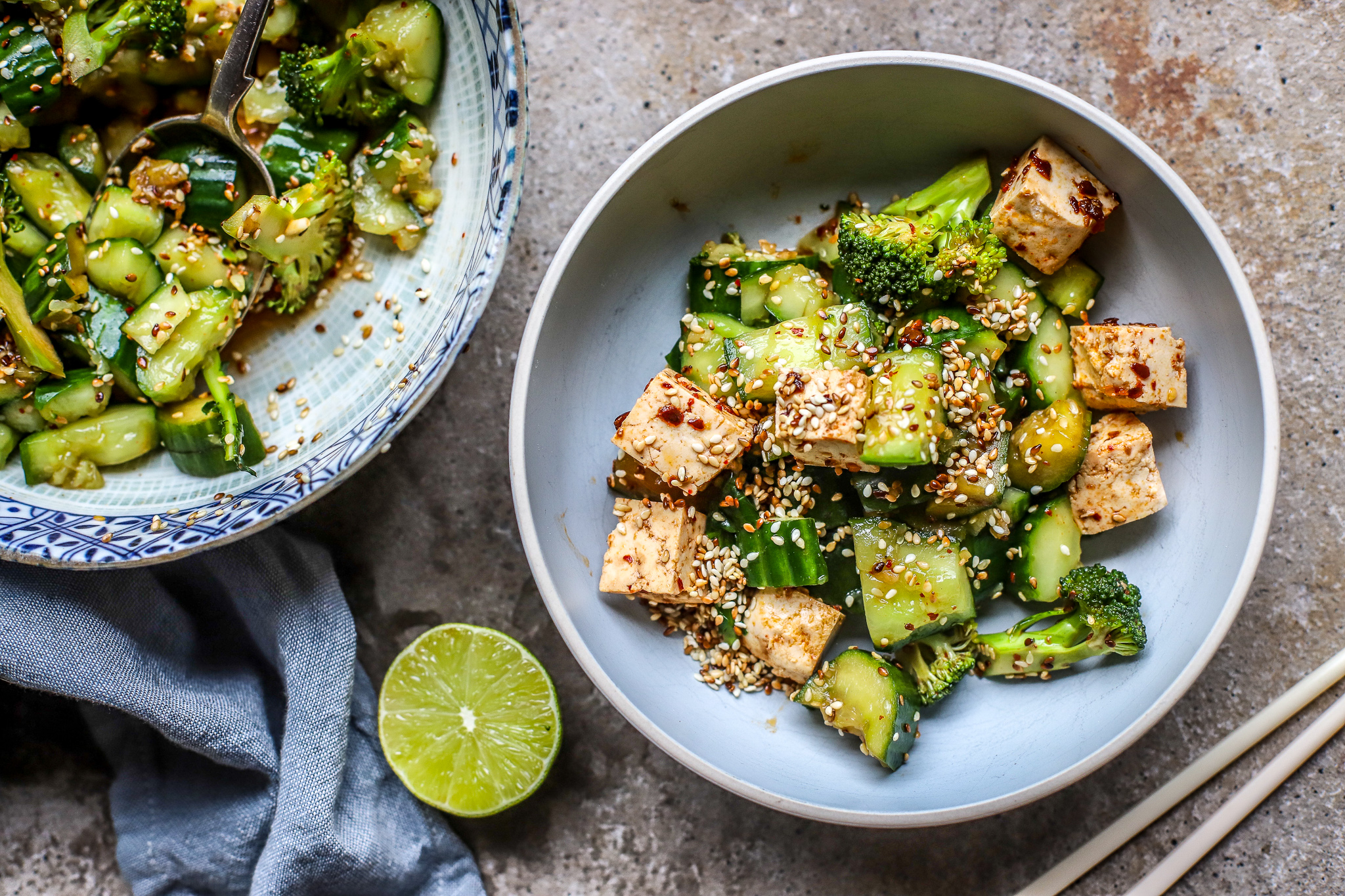 smashed cucumber salad in bowls with tofu on concrete background