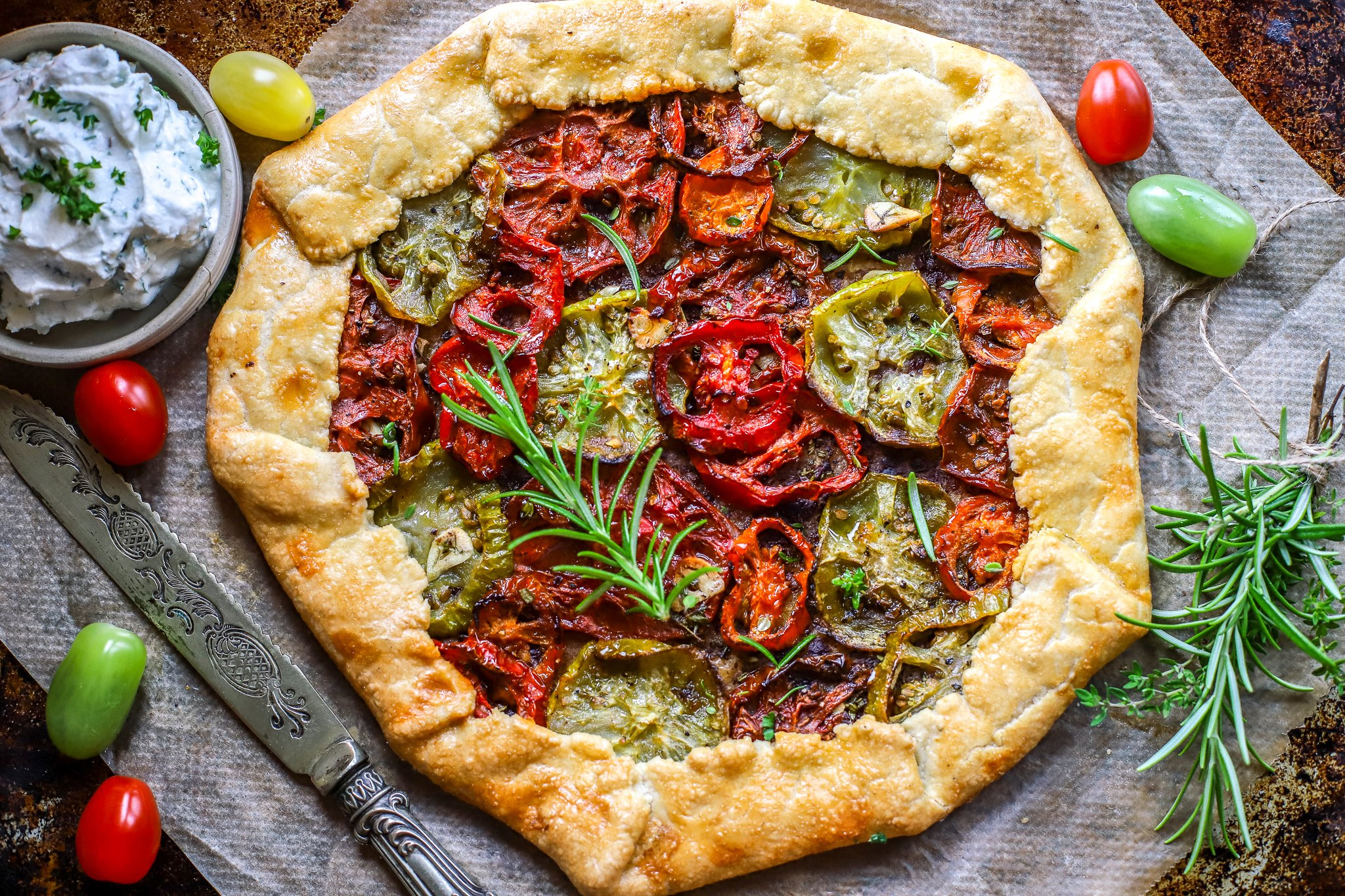 roasted tomato galette on baking tray with ricotta dip and herbs