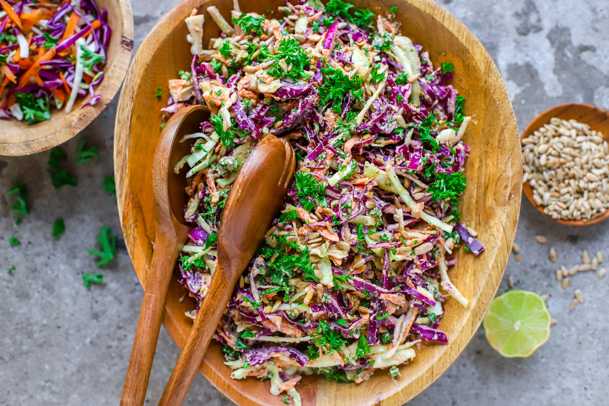 colouful coleslaw in wooden bowl with wooden spoons on concrete background