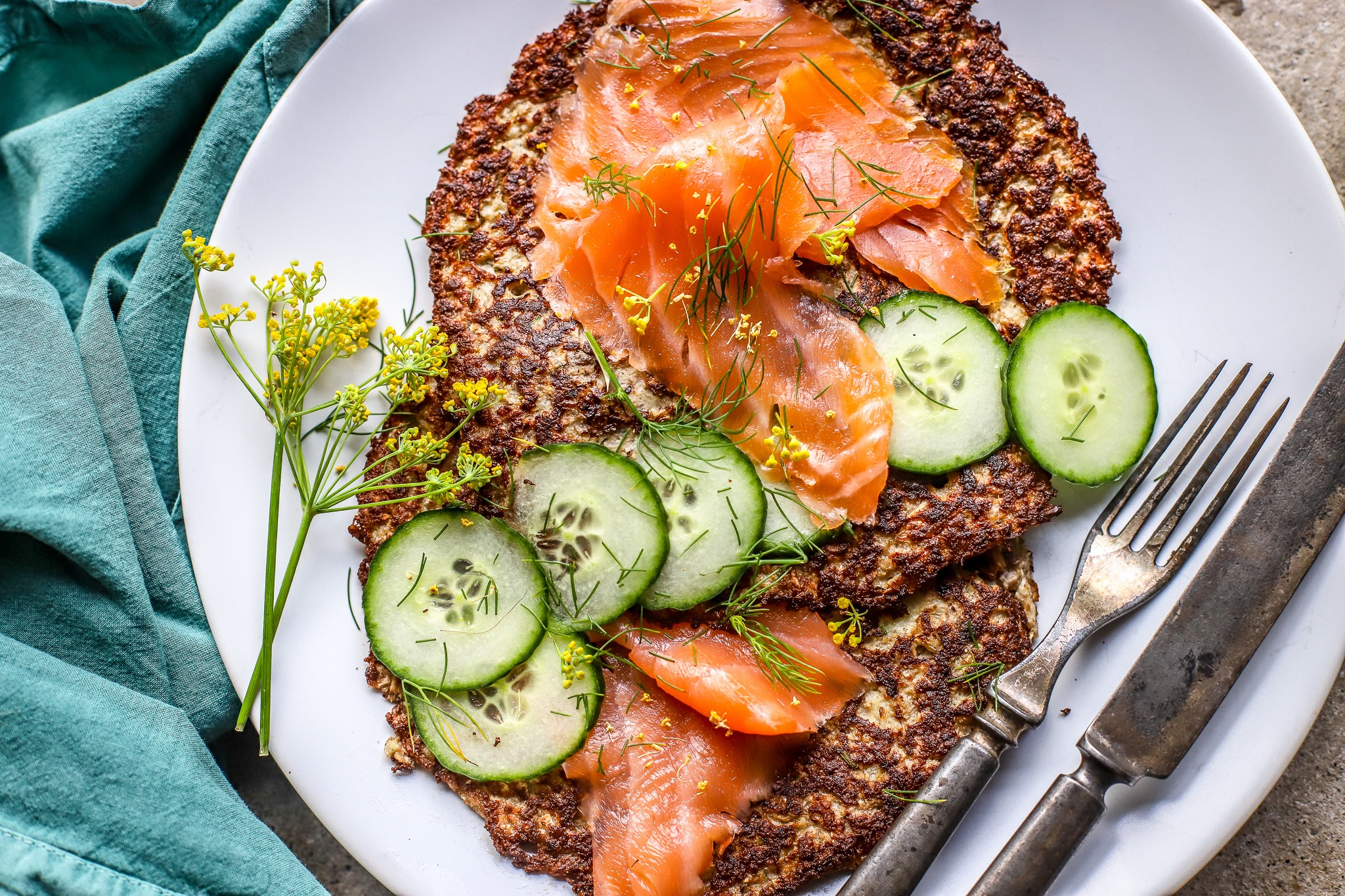 scandinavian cauliflower rosti with smoked salmon and cucumber slices with pollen close shot on white plate